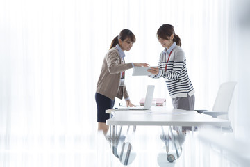 Two women looking at tablet in the office