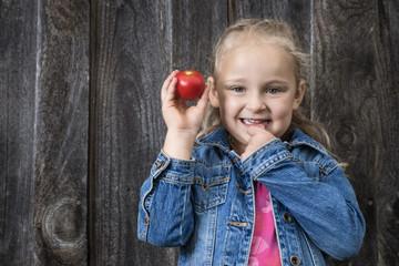 Hübsches kleines Mädchen mit roter Tomate