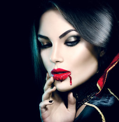 Beauty sexy vampire girl with dripping blood on her mouth