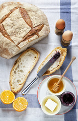 Breakfast table. Bread, boiled eggs, butter, honey, marmalade, o
