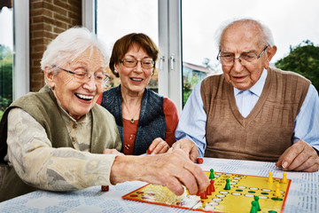 Elderly couple and daughter, playing board game