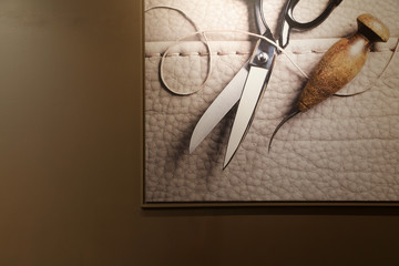 Art photo of scissors, leather and thread in photo frame on wall