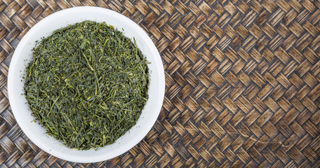 Dried green tea leaves in white bowl over wicker background