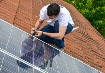 electrician on roof with curved tiles measuring for solar panel