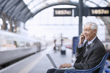 Senior businessman takes a mobile call on a train station platform.