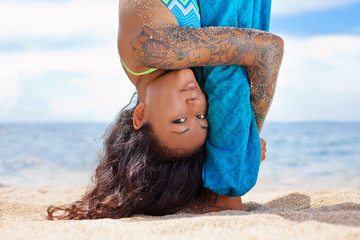 asian young woman doing yoga on the beach