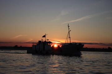 Корабль плывет по реке на закате солнца