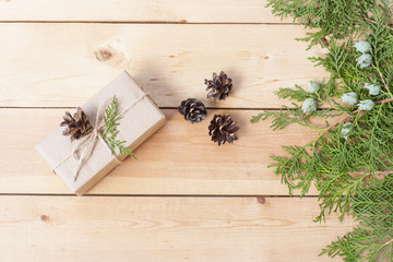 Christmas Gift, nuts, cones and green arborvitae branch on a wooden table