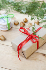 Christmas gift and cookies, nuts, cones, cinnamon and green arborvitae branch on a wooden table