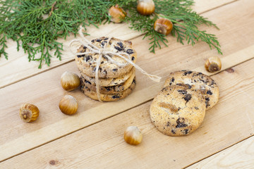 Homemade Christmas cookies with chocolate, nuts, cones, cinnamon and green arborvitae branch on a wooden table