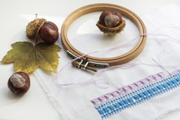Mature chestnuts, autumn leaves and needlework on white background