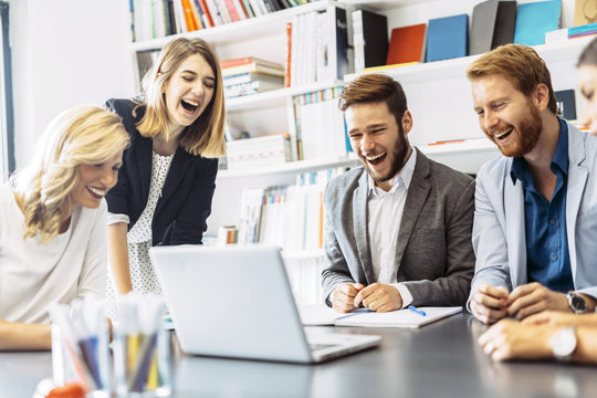Cheerful people laughing in office