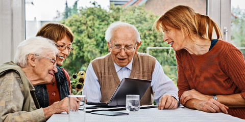Elderly couple and daughters, looking at laptop screen