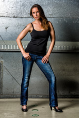 Trendy Woman in blue jeans posing in the grungy underground
