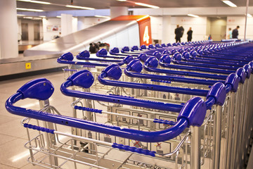 Row of trolleys with baggage pickup carousel at the background.