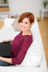 lächelnde frau mit laptop schaut nach oben