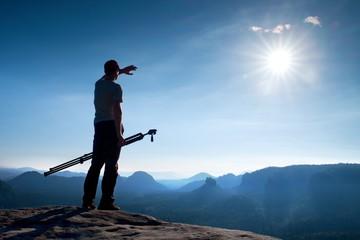 Photo enthusiast stay with tripod on cliff and thinking. Dreamy fogy landscape, blue misty sunrise in a beautiful valley below