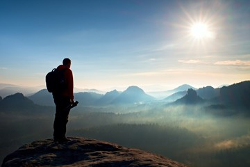 Alone  photographer with heavy backpack and tripod in hand on rocky cliff and watching down to deep misty valley bellow