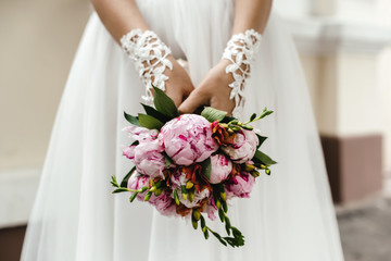 wedding bouquet flowers with pions in bride hand
