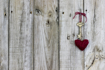 Skeleton key and red rope heart hanging on rustic wood door