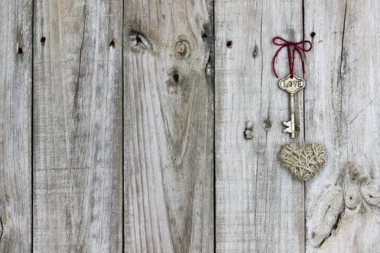 Skeleton key and rope heart hanging on rustic wood door