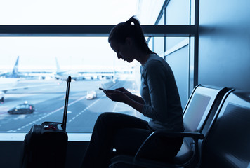 Woman using mobile smart phone at the airport