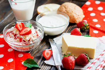 healthy breakfast of fruit and dairy products , cottage cheese with sour cream and milk, butter and roll , strawberries and syrup on a wooden background