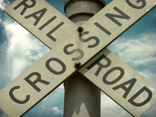 aged and worn vintage photo of railroad crossing sign