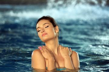 Beautiful young woman at swimming pool
