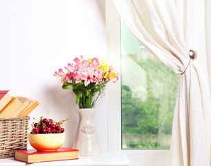 Alstroemeria flowers with cherries and book in vase