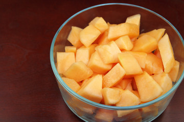 Cantaloupe Pieces in a Clear Glass Bowl on Wood
