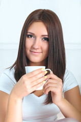 Attractive girl in shirt enjoying a cup of coffee.