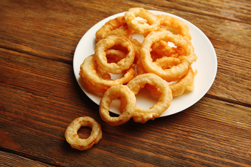 Chips rings on plate on wooden background