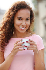 Close up portrait of pretty young woman in pink dress drinking coffee at summer terrace