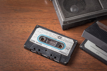Vintage tape cassette with old radio on wooden table background