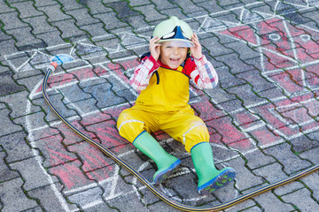 Funny adorable child of four years having fun with fire truck pi
