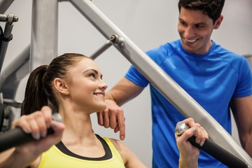 Confident woman using weights machine with trainer