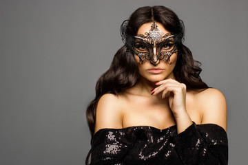 Sexy girl in a Venetian mask looking straight