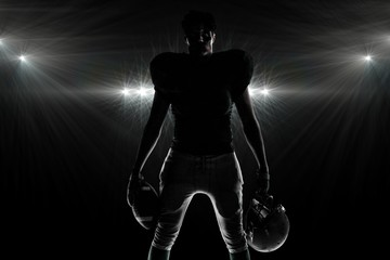 Composite image of silhouette american football player