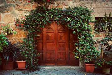 Fototapete - Retro wooden door outside old Italian house in a small town of Pienza, Italy. Vintage