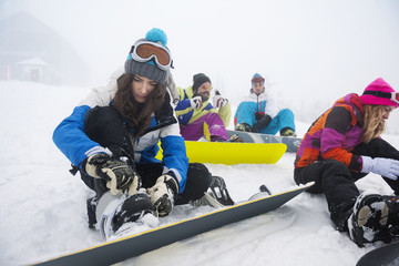 Women focused on clasping ski shoes.