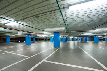 empty grey parking with colored blue columns without cars