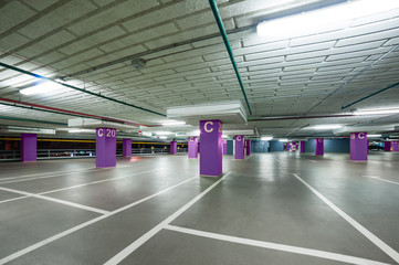 empty grey parking with colored violet columns without cars