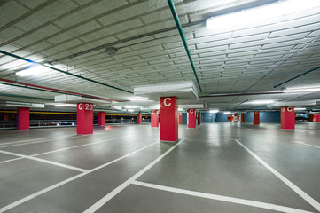 empty grey parking with colored red columns without cars