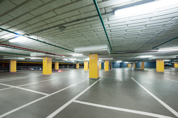 empty grey parking with colored yellow columns without cars