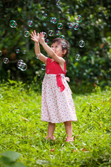 Asian girl catches soap bubbles on nature background. Outdoors.