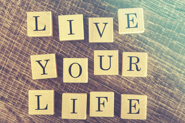 Wooden letter cubes forming Live Your Life message. Cross processed image for vintage look