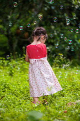 Girl playing with soap bubbles on nature background. Outdoors