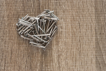 Nails forming a heart on a wooden bench.