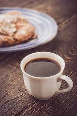 Cup of coffee with blurred croissant   on the blue ceramic plate vertical